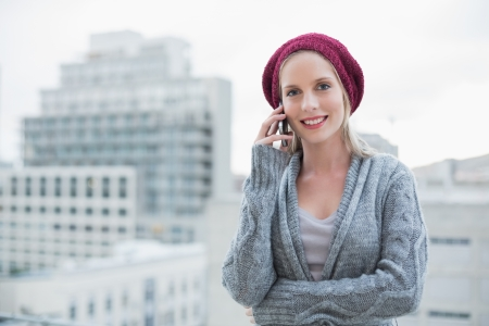 young adult: Smiling pretty blonde on the phone outdoors Stock Photo
