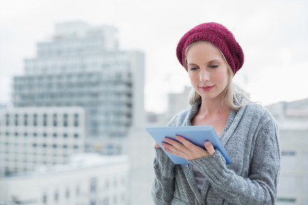 Peaceful pretty blonde using tablet pc outdoors on urban background photo