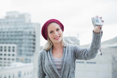 Smiling pretty blonde taking a self picture outdoors  photo