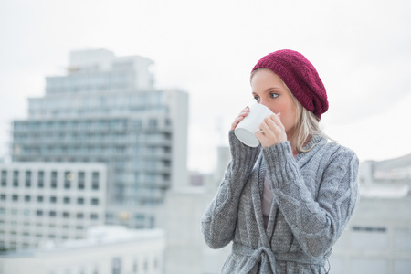 Peaceful gorgeous blonde drinking coffee outdoors on urban background photo