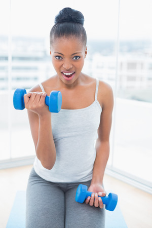 woman lifting weights: Woman sitting on exercise mat working out with dumbbell at home Stock Photo