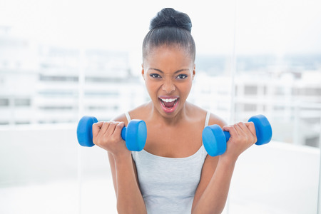 woman working out: Woman working out with dumbbells at home