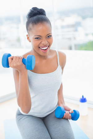 exerted: Exerted woman working out with dumbbell while looking at camera