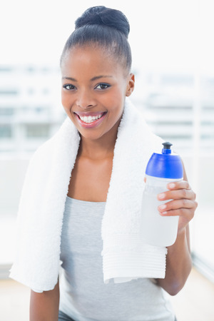 Smiling woman with towel over neck holding sports bottle while looking at camera photo