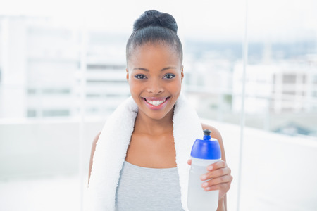 Fit smiling woman with towel around her neck holding sports bottle and looking at camera photo
