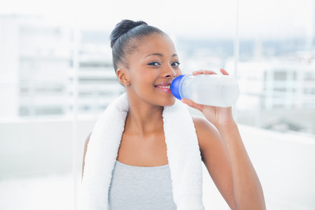 Fit woman with towel around her neck drinking water while looking at camera at home photo