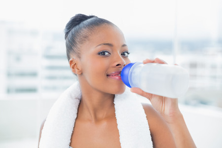 Smiling woman with towel around her neck drinking water while looking at camera photo