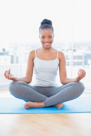 Smiling woman practicing yoga while looking at camera in bright room at home photo