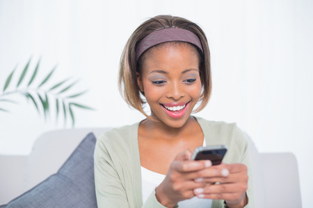 Pretty woman sitting on sofa text messaging in bright living room photo