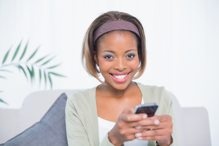 hairband: Cheerful elegant woman sitting on sofa text messaging while looking at camera Stock Photo