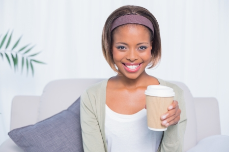 hairband: Smiling woman sitting on sofa holding coffee and looking at camera
