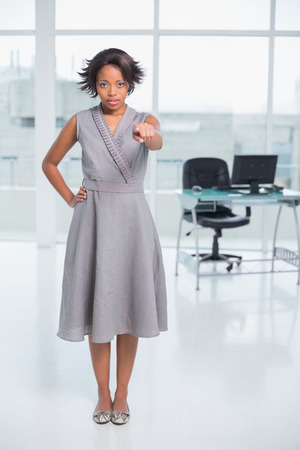 unsmiling: Serious businesswoman standing in her office and pointing at camera Stock Photo