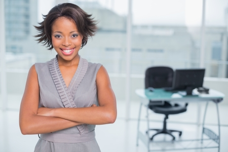 classy woman: Smiling businesswoman standing in office and crossing her arms while looking at camera