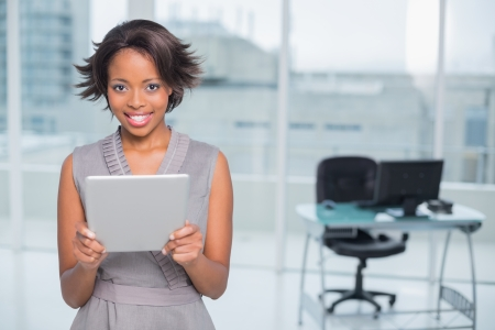 classy woman: Smiling businesswoman standing in her office and holding tablet while looing at camera