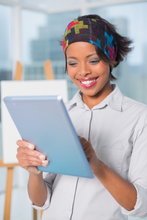 hairband: Cheerful artist using tablet in her studio Stock Photo