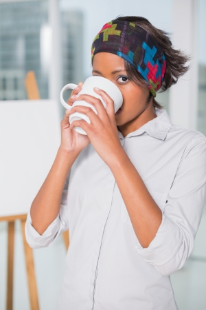 hairband: Artistic woman drinking a coffee in her studio Stock Photo