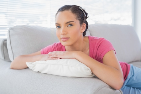 Attractive woman lying on sofa and looking at camera photo