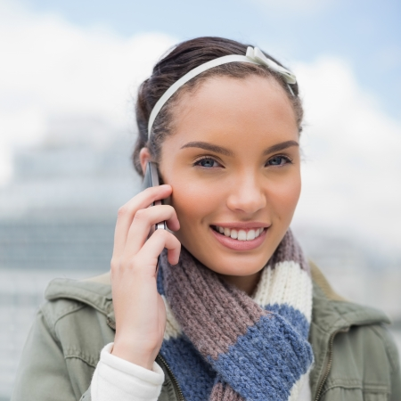 hairband: Close up view of attractive woman talking on phone and looking at camera outside