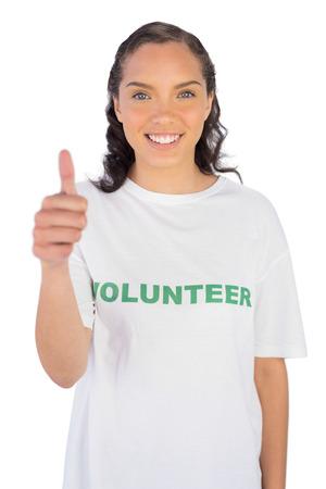 altruism: Mujer bonita con el voluntario pulgar hacia arriba contra el fondo blanco