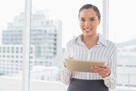 Happy businesswoman using tablet while looking at camera and standing in her office photo