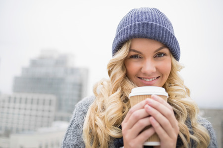 Cheerful pretty blonde having coffee outdoors on urban  photo