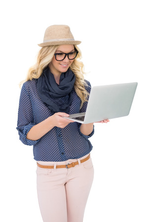 Smiling trendy blonde holding laptop on white  photo