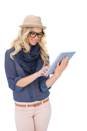Smiling trendy blonde using tablet computer on white  photo