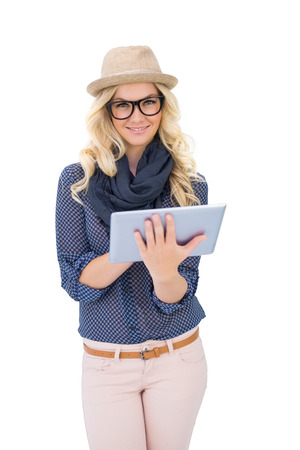 Smiling trendy blonde using tablet pc on white  photo