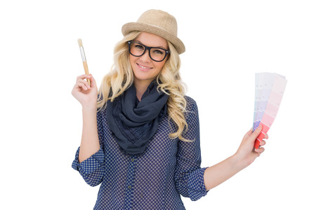 Cheerful trendy blonde with classy glasses holding color chart on white  photo