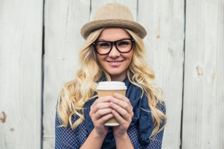 Cheerful fashionable blonde holding coffee outdoors on wooden  Stock Photo