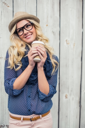 Happy fashionable blonde holding coffee outdoors on wooden  photo
