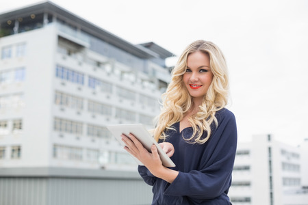 Smiling gorgeous blonde with red lips using tablet  photo