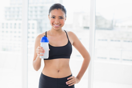 Content dark haired model in sportswear drinking water in bright fitness studio photo