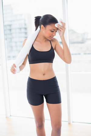 Exhausted dark haired model in sportswear drying herself with a towel in bright fitness studio photo