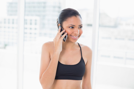 Pleased dark haired model in sportswear making a phone call in bright fitness studio photo