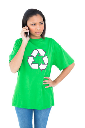 dark haired: Unsmiling dark haired environmental activist making a phone call on white