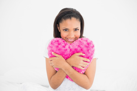 Delighted young dark haired model cuddling a heart-shaped pillow in bright bedroom photo
