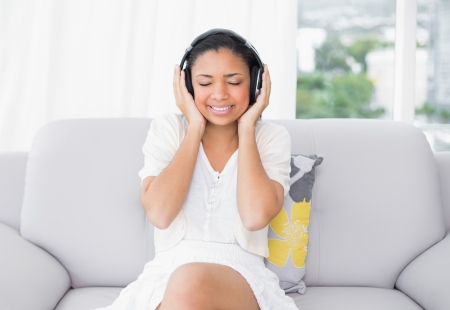 dark haired woman: Peaceful young dark haired woman in white clothes listening to music in a living room