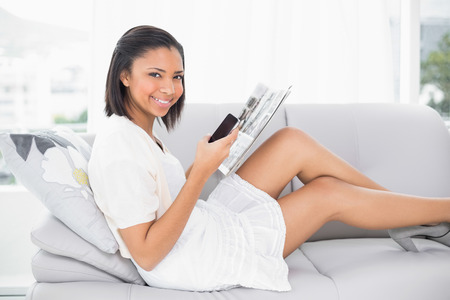 dark haired woman: Amused young dark haired woman in white clothes reading a magazine in a living room Stock Photo