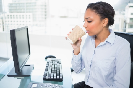 Relaxed young dark haired businesswoman drinking coffee in bright office photo