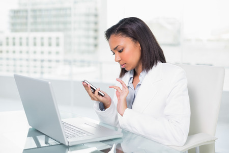 Serious young dark haired businesswoman using a mobile phone in bright office photo