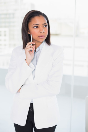 Attractive young dark haired businesswoman posing looking away in bright office Stock Photo - 25403546