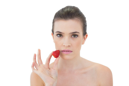 Serious natural brown haired model holding a strawberry on white  photo