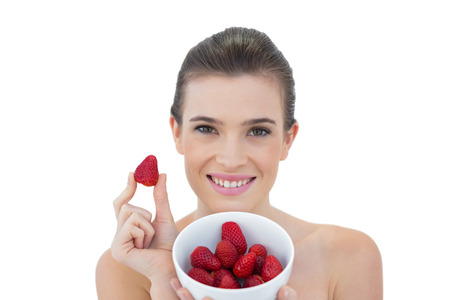 Beautiful natural brown haired model showing a bowl of strawberries on white  photo