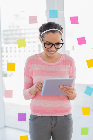 Smiling artist using tablet while standing in her creative office photo
