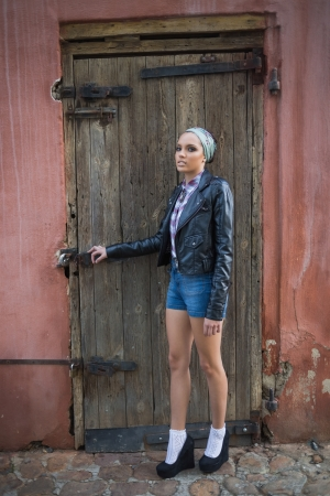 Attractive woman with hairband posing and looking at camera in front of a wooden door photo