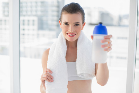 Content fit brown haired model in sportswear carrying a bottle and a towel in bright room photo