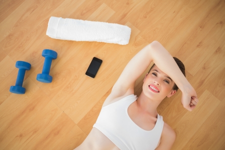 Tired fit brown haired model in sportswear relaxing after sport lying on wooden floor photo