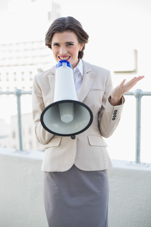 Attractive stylish brown haired businesswoman speaking in a megaphone outdoors photo
