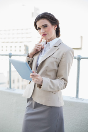 Thinking stylish brown haired businesswoman holding a tablet pc outdoors photo